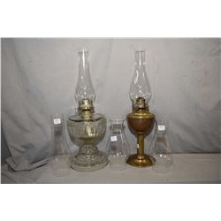 Two vintage oil lamps including brass with clear hurricane and colourless with greek key embossed fo