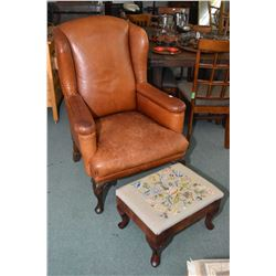 Vintage well worn tanned leather wing back chair with cabriole supports a vintage needlepoint uphols
