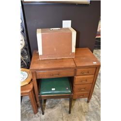 Vintage mahogany sewing machine cabinet with stool and a portable Anker electric sewing machine