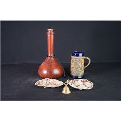 A Spanish Wine Bottle, A Water Cup, Two Small Dishes and a Copper Bell.