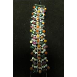 Multi coloroed agate beads intertwined with gold and silver on a black beaded background creates thi