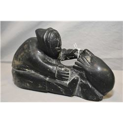 Carved soapstone carving of a fisherman rescuing his catch, initialled and numbered on under side, 1