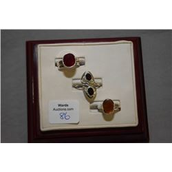 Three sterling silver and gemstone rings including garnet, lab created ruby and ammonite