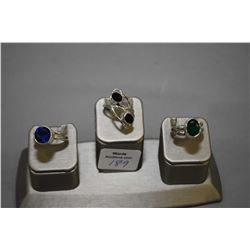 Three sterling silver rings set with gemstones including garnet, and lab created sapphire and emeral