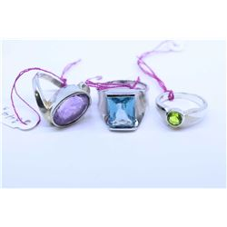 Three sterling silver and gemstone set ring including amethyst and blue topaz plus a peridot like ge
