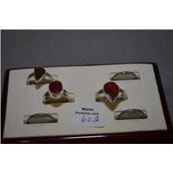 Three sterling silver rings including lab created ruby and two ammonite