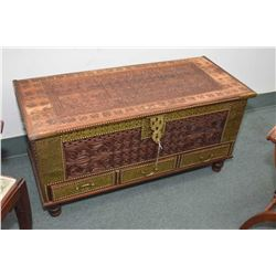 Decorative hand carved lidded wooden chest with heavy brass handles and latch and hand hammered bras