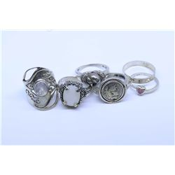 Six sterling silver rings including gemstone set rings, coin rings, band etc.