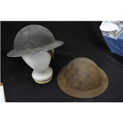 Two vintage WWI helmets with liners