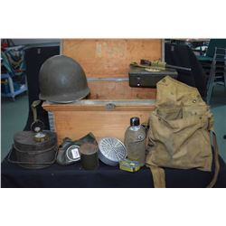 Small wooden foot locker, empty mess kit, helmet, gas mask, first aid kit etc.