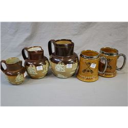 Three Royal Doulton salt glazed pitchers in graduated sizes and two curling motif tankards