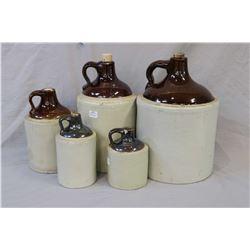 Five glazed stoneware jugs in graduating size including two gallon, one gallon, half gallon, quart a