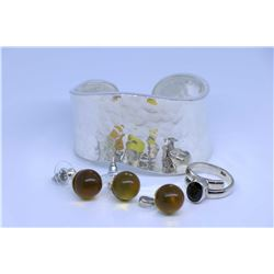 Sterling silver and garnet ring, a golden amber pendant and earring set and a white metal bangle
