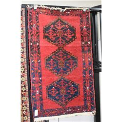 Wool throw carpet with triple medallion, red background with highlights in blue, orange, green etc.
