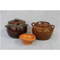 Three pieces of glazes pottery including a Sunburst, Canada lidded bean pot, a Medalta potteries bea