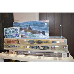 Five unassembled plastic model kits including three destroyer/battleships, a submarine and an aircra