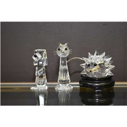 Three small Swarovski Crystal figures including a hedgehog, a stylized dog and cat