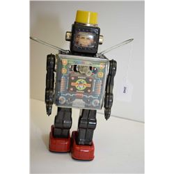 Pressed tin battery operated Robot with light up helmet and shooting ray gun, made in Japan, 11  in