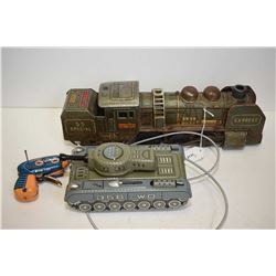 Two vintage tin toys including a mechanical cable operated tank and a battery operated train