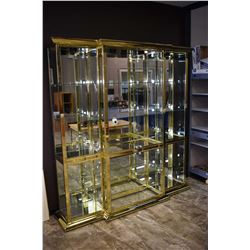 Large three piece brass style glass display cabinet with glass shelving, illumination and mirrored b