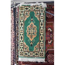 Small wool scatter rug with emerald green back and center medallion with taupe and black highlights,