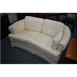 White on white upholstered loveseat made by Barrymore