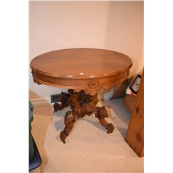 Antique walnut occasional table with heavily carved base
