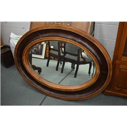 Large modern oval bevelled wall mirror with leather wrapped frame with nail head decoration, overall