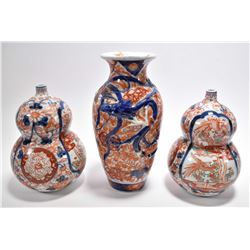 Three pieces of early unmarked Oriental porcelain including a pair of gourd shaped vessels with hand