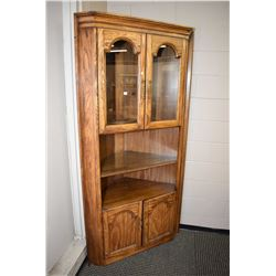 Semi contemporary oak corner cabinet with two glazed doors with adjustable shelf