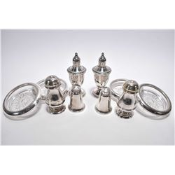 Three pairs of sterling silver shakers and a set of four glass coasters with sterling collars
