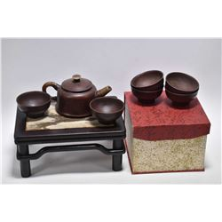 "Set of Oriental purple clay tea items and a small ""landscape stone"" top tan wooden stand, 4"" in heig"
