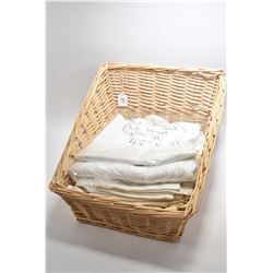 Basket containing a selection of linens including tablecloths, napkins etc.