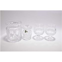 Four pieces of Waterford crystal including a spooner, two brandy snifters and a lidded biscuit barre