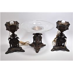 Three piece garniture including a pair of Griffin motif lamps and a center pedestal stand with glass