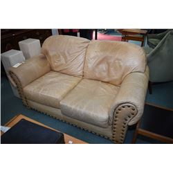 Genuine leather sand tone loveseat and matching armchair, both with large nail head decoration