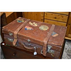 Antique leather suitcase with travel stickers including Paris, Zurich, Brussels etc.