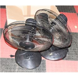 A PAIR OF BLACK ROTATING TABLE FANS