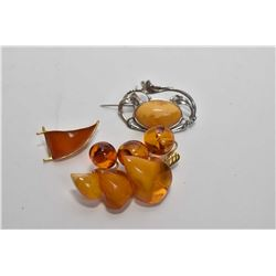 Three amber brooches including Baltic amber and gold plate brooch, Nouveau style silver brooch, and