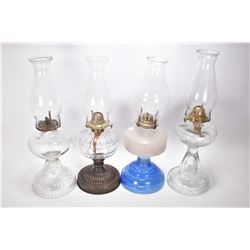 Four vintage oil lamps including three colourless including one with metal base and a milk glass wit