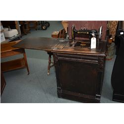 Antique Eaton treadle sewing machine in fully enclosed oak cabinet
