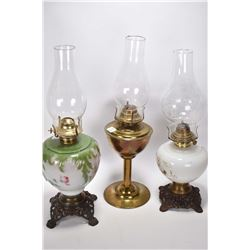 Two vintage oil lamps with glass painted fonts plus a brass oil lamp, all with clear chimneys
