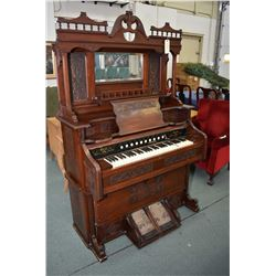 Antique pump organ made by Bell Organ and Piano Company with tall decorative back and bevelled mirro