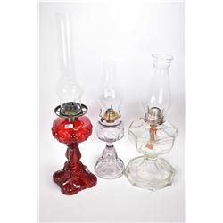 Three pressed glass oil lamps including two colourless including one turning purple and a ruby glass