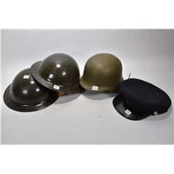 Three vintage army helmets and an officer's hat