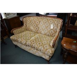 Antique loveseat with gold brocade upholstery and decorative show wood