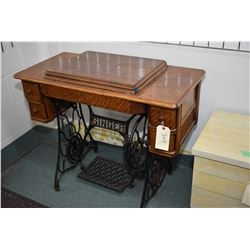Antique Singer treadle sewing machine in oak and metal cabinet