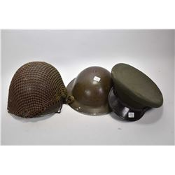 Two military helmets and an officer's hat