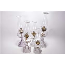 Set of five matching and graduated sized colourless pressed glass oil lamps