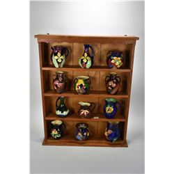 Wall mount four tier display with twelve pieces of Tunstall handpainted semi-porcelain cabinet piece